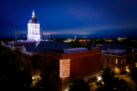 Aerial photo of projected poetry and illuminated Jesse Hall dome at night.